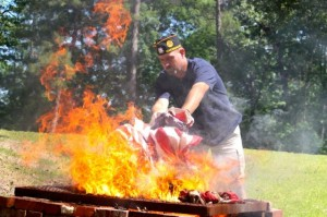 Kevin Spradlin | PeeDeePost.com Wayne Johnson, first vice commander for American Legion Post 147, throws a handful of unserviceable flags into the flames.