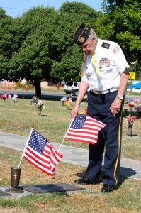 Kevin Spradlin | PeeDeePost.com Hamlet resident Jimmy Brigman, of Disabled American Veterans, places a U.S. flag at Richmond County Memorial Park on East Broad Avenue in Rockingham.