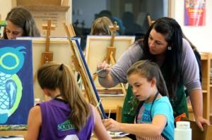Kevin Spradlin | PeeDeePost.com Artist Nikki Cherry helps sixth-grader Makenzie Taylor.