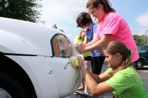 Kevin Spradlin | PeeDeePost.com From top to bottom: Megan McGuire, Rebecca Clay, Ashley McGuire and Jessica Matheson help scrub the bumper of a Ford pick-up truck Saturday morning at First United Methodist Church in downtown Rockingham.