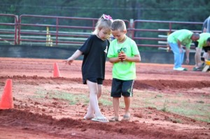 Kevin Spradlin | PeeDeePostcom Taylor Crouch, 5, left, plays with a friend Friday night at the Ellerbe Lions Club park during the Tossing for Taylor corn hole tournament.