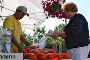 Kevin Spradlin | PeeDeePost.com Rachel Barker, of Rockingham, prepares to pay for her purchase of tomatoes and other homegrown goodies from the David's Produce booth Wednesday at the Richmond County Farmers' Market in downtown Rockingham.