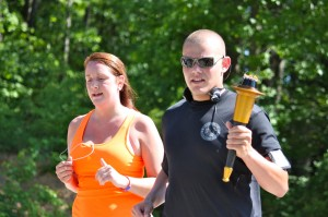 Kevin Spradlin | PeeDeePost.com Wendi Clewis and Thomas Grooms approach the Rotary Lodge at Hinson Lake to finish Richmond County's leg of the 2014 North Carolina Law Enforcement Torch Run for Special Olympics.