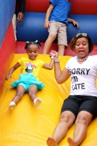 Kevin Spradlin | PeeDeePost.com Tiffany Porter, of Wilmington, and Sydnee, 4, take a ride down the inflatable slide on Saturday at Hamlet Memorial Park. The two are cousins of Melvin Ingram, who funded the day's festivities.