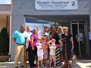 Kevin Spradlin | PeeDeePost.com Front row, left to right: Grayson Wrenn, 5, Neely Turner, 7, and C.J. Turner, 5, work the giant pair of scissors at the ribbon-cutting ceremony Friday at Modern Woodmen in downtown Rockingham.