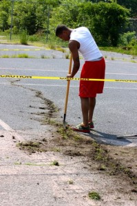 Kevin Spradlin | PeeDeePost.com Quentin Gore, 19, and family members worked to get rid of weeds coming up through the long, wide cracks of the Dobbins Heights Community Park basketball court.