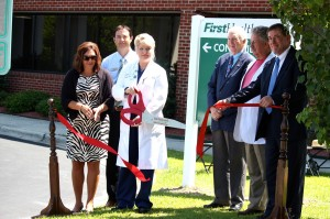 Kevin Spradlin | PeeDeePost.com Dr. Lisa Cowan, with scissors, stands with (left to right): Emily Tucker, Richmond County Chamber of Commerce president; Brian Baucom, vice chair, Chamber of Commerce board of directors; Rockingham Mayor Steve Morris; County Commissioner Don Bryant; and John Jackson, CEO of FirstHealth Richmond.