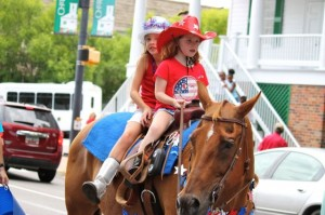 Kevin Spradlin | PeeDeePost.com Kody Bozard, in red cowgirl hat, and friend Natalee Batchelor ride Lena into second place of the Most Patriotic division on Thursday in Cheraw.