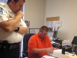 Kevin Spradlin | PeeDeePost.com Hamlet Police Chief Rodney Tucker, right, and Capt M. Scott Waters review the case file on the 2006 murder of Michael McLean.