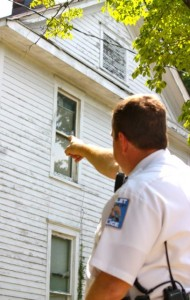 Kevin Spradlin | PeeDeePost.com Capt. M. Scott Waters points to the two-story boarding house on Lackey Street where Michael McLean lived in January 2006. McLean's body was found just around the corner on Oak Avenue, the victim of a fatal beating.