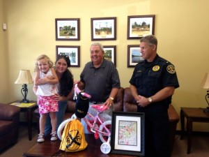 Kevin Spradlin | PeeDeePost.com CSX Railroad Police Lt. T.V. Kirkley, of Operation Lifesaver, right, and Jim Graham, president of the Hamlet Depot & Museums board of directors, present Peyton Maree, 3, of Hamlet, a bicycle and other prizes for being randomly selected as the contest winner from among 133 entries.