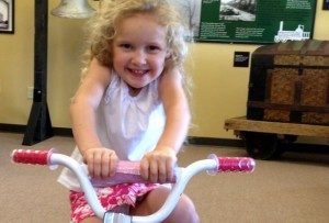 Kevin Spradlin | PeeDeePost.com Peyton Maree, 3, of  Hamlet, enjoys her first ride on her first bicycle, a prize awarded to her as winner of the Stay Back from the Tracks