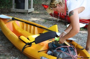 Kevin Spradlin | PeeDeePost.com Mari Bennett, owner of LMO Paradise Rentals, checks her gear before launching her kayak into Hitchcock Creek for a clean-up trip from Steele Street to Cordova.