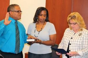 Kevin Spradlin | PeeDeePost.com Daryl Mason, left, is sworn in by Richmond County Clerk of Superior Court Vickie Daniel as Mason's wife, Teresa, holds the Bible.