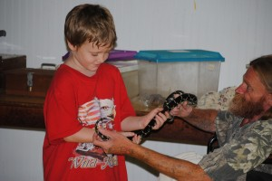 """Dena Evans   PeeDeePost.com Cord Bullard was fearless and inquisitive as they surrounded the """"Snake Man"""" for some one-on-one interaction with a milk snake. Seeing the children, initially hesitant to touch the snake, eagerly seek out this interaction supports Frank Prosser's mission in conducting these education sessions."""