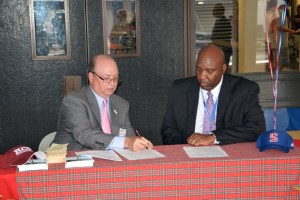 A Richmond Community College photo RCC President Dr. Dale McInnis (left) and SCS Superintendent Dr. Ronald Hargrave sign an expanded partnership agreement Tuesday night at Scotland High School. The new agreement expands the number of classes that RCC will be offering on the Scotland High campus.