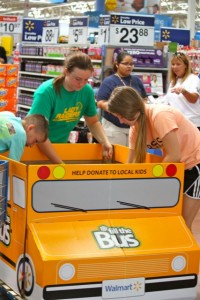 Kevin Spradlin | PeeDeePost.com Will Thompson, Taylor Parrish and Jenna Staub collect donated school supplies from inside Walmart to take to the Richmond County school bus outside in the parking lot. The bus will deliver a load of supplies to the central office in Hamlet. From there, school social workers will help distribute the supplies to those who most need them.