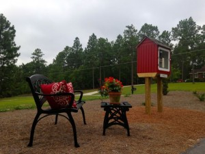 Kevin Spradlin | PeeDeePost.com The bench was rarely used in the first hour of the Grand Opening of the Little Free Library on Fairway Drive in the Pine Lakes subdivision, as neighbors and readers were too busy browsing the many books available by Dale and Susan Furr.