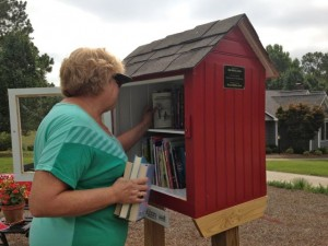 Kevin Spradlin | PeeDeePost.com Pine Lakes resident Beth Ray brings three and takes a couple books from the Little Free Library on Fairway Drive established by Dale and Susan Furr.