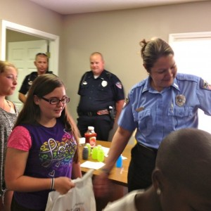 Kevin Spradlin | PeeDeePost.com T.M. Prisk, a telecommunicator with the Rockingham Police Department, helps distribute school supplies on Monday in the E.R. Martin Community Policing Center situated between the Gardenwood and Crown Poine apartment complexes.