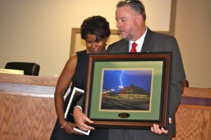 "Kevin Spradlin | PeeDeePost.com Councilman Pat Preslar presents to outgoing City Manager a framed photo taken by Jimmy McDonald of a June lightning storm over the Hamlet Depot. The photo was inscribed with the phrase, ""Weather the Storm."""