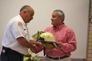 Kevin Spradlin | PeeDeePost.com Rockingham City Manager Monty Crump, right, presents Fire Chief Charles Gardner with his helmet, albeit cleaned up a bit, during a retirement ceremony Tuesday at the fire hall on Lawrence Street.