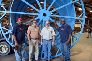 Submitted photo From left, Ferro Fab welder Anthony Allred, RCC Director of Customized Training Lee Eller, Ferro Fab Plant Manager Malcolm McLester and Ferro Fab welder Ronald Legrande stand with a giant spool built by welders at the Hamlet based industry.