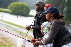 Kevin Spradlin | PeeDeePost.com Denika McCormick helps Imari, 6, reel in a fish on Saturday at the Cheraw Fish Hatchery.