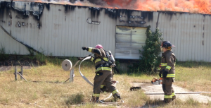 Kevin Spradlin | PeeDeePost.com When there was still hope for more than managing the blaze, firefighters with the Northside Volunteer Fire Department unrolled hoses in order to keep the damage to a minimum. They succeeded in preventing the flames from reaching any of the many outbuildings and plywood-built vendor stalls.