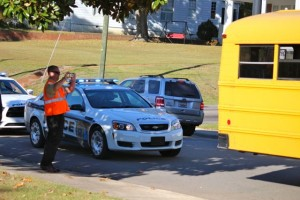 Kevin Spradlin | PeeDeePost.com A Rockingham Police Department officer takes a photo of some of the damage to the bus caused when the driver turned the corner and grazed a telephone pole.