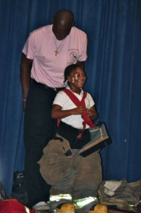 Kevin Spradlin | PeeDeePost.com Lt. Wayne Covington helps a student get into oversized firefighting gear on stage at L.J. Bell Elementary School.