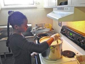 Photo by Kevin Spradlin Amiya Griffin, then 11, takes a turn at the stove during the 2013 version of the Watkins-Kendall Thanksgiving dinner in Dobbins Heights.