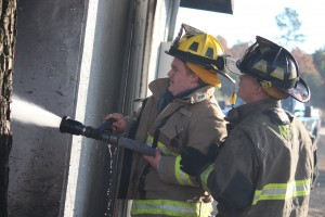 Kevin Spradlin | PeeDeePost.com Volunteer firefighters from Hoffman and Northside fire departments work to put out flames creeping into a storage building of a nearby church.