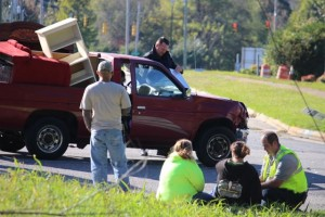 Kevin Spradlin | PeeDeePost.com Lt. Michabel Mabe, right, of the Rockingham Fire Department, tends to a female passenger of the red pickup truck Sunday afternoon after a two-vehicle collision.