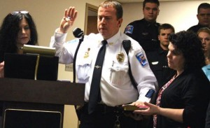 Kevin Spradlin | PeeDeePost.com Hamlet Police Chief Scott Waters takes the oath of office from City Clerk Tammy Kirkley on Monday with wife Laurie, his three daughters and police officers and emergency dispatchers behind him.