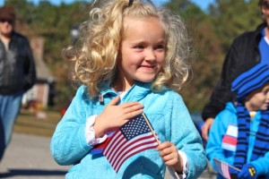 Kevin Spradlin | PeeDeePost.com A member of Laura Lee Martin's kindergarten class at Washington Street Elementary School smiles and holds a flag before the start of the 4th annual Salute to Veterans. The students led the audience in the Pledge of Allegiance.