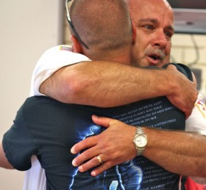 Kevin Spradlin | PeeDeePost.com Rockingham Fire Chief Charles Gardner embraces his son, David Gardner, himself a firefighter with the city of Burgaw, during an emotional farewell ceremony Tuesday at the fire hall.
