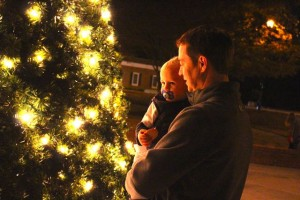 Kevin Spradlin | PeeDeePost.com Brian Baucom, of Rockingham, holds 20-month-old Maddox. Also at the Tree Lighting Ceremony Tuesday was wife Genny, Braden, 5, and Maddox's twin brother, Owen.