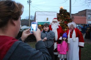 Kevin Spradlin | PeeDeePost. Melissa Barber and sister Jessica Duncan, of Ellerbe, take a picture of Joshua, 12, and Taylor, 4, with Santa and Mrs. Claus in front of the town Christmas tree