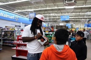 Kevin Spradlin | PeeDeePost.com Dannell Ellerbe signs autographs for children for whom he funded a Christmas shopping trip at Walmart on Dec. 22 in Rockingham.