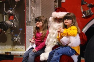 MacKenzie Spradlin | PeeDeePost.com MaKayla Brown and her twin sister McKenzie, in yellow, speak with Santa Claus on Saturday at the Hamlet Fire Department.
