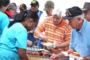 Kevin Spradlin | PeeDeePost.com Jack Hudson, right, and Ronald Wallace, in orange, go through the buffet-style line for chicken, baked beans, slaw and plenty more on Saturday at the North Carolina National Guard Armory in Hamlet during the inaugural Celebration of Armed Forces.