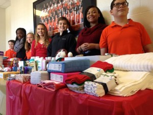 Kevin Spradlin | PeeDeePost.com Douglas McDonald, Allexis Swiney, MacKenzie Spradlin, Kylie McDonald, Wes Boyette, Jen'Nice Conrad and Brandon Swallow stand by tables of goods at Rockingham Middle School. Members of the student body have spent the past two weeks collecting the items and bringing them to school. The items will be donated to the Place of Grace Rescue Mission.