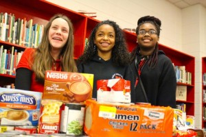 Kevin Spradlin | PeeDeePost.com From left to right: Caitlyn Daniel, SGA vice president; Jayla Copeland, secretary; and Jadah Littles, treasurer, stand with a portion of food items donated by the Hamlet Middle School student body.