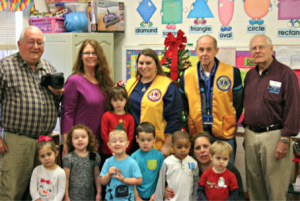 Submitted photo Lion Phil Bradley, Preschool Director Cindy Bostick, Lion Kristen Cook, Lion Winfred Pence, Lion Harvey Auman and hidden among the children is Lion Keri Cook, coordinator.