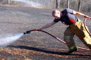Kevin Spradlin | PeeDeePost.com A Northside Volunteer Fire Department firefighter pulls a fire hose from a truck to reach the flames of a controlled burn that got away.