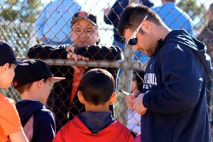 Kevin Spradlin | PeeDeePost.com Hamlet Middle School Principal Jim Butler looks on as Kyle Roller signs autographs after a hitting session on Saturday in the inaugural Red Ram Hit-a-thon.