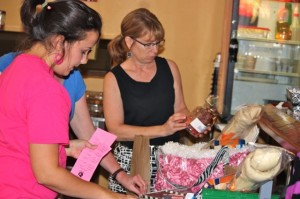 Kevin Spradlin | PeeDeePost.com Allison Sweatt, of Richmond County Animal Advocates (left), and Amy Guinn, of Cafe on Main, sort raffle items during the inaugural Spay-ghetti dinner June 15 in Hamlet. Owner Amy Guinn has decided to close the restaurant effective immediately.