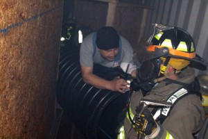Kevin Spradlin | PeeDeePost.com Capt. Julian Whitney helps firefighters check their air supply inside the pitch-black corridors of a training exercise.