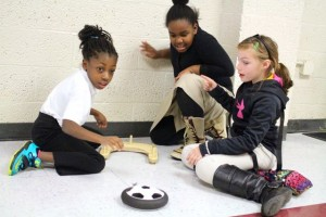 Kevin Spradlin | PeeDeePost.com Students use a hover puck and a rubber band to learn about  mass and acceleration.